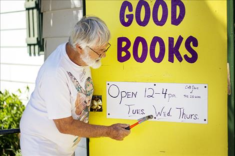 Dave Marshall hammers a sign on the door with the store's hours.