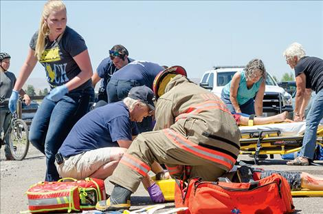 Ambulance crews and firefighters help victims  in mock rescue.