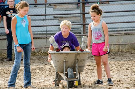 A farmer olympics competitor peeks out of a wheelbarrow as he prepares to race with teammates across the arena.