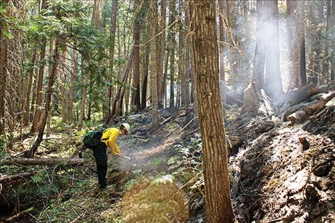 Information Officer Jacob Welsh stops to stirs some coals along the hand line, an area the fire fighters clear cut to help prevent the fire's spreading.
