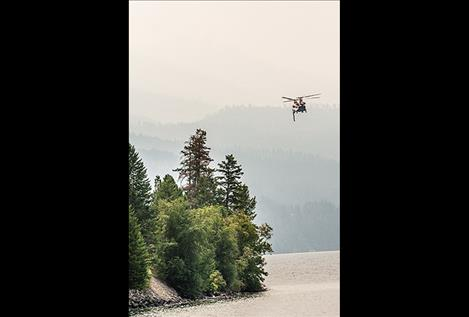 A Chinook (CH-47D) helicopter scoops water from Blue Bay on Friday morning. It has a capacity of carrying 1500 gallons of water with a 4 minute turn-around time to the blaze east of the Flathead Lake.