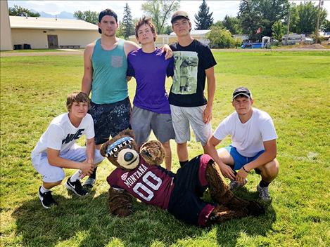 Charlo High School seniors Tyson Petticrew, Chandler Krahn, Sabin Perry, Shad Anderson and Brady Fryberger pose for a photo with UM mascot Monte Bear.