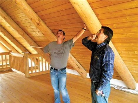 Jay Brewer and CSKT Maintenance Department Manager John Neiss look at progress in the upstairs of the main house at the Kuki A'kilwiy sober living house north of Hot Springs.