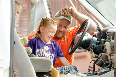 Volunteer firefighter Matt Hout shows his daughter, Peyton, 6, the inside of the ambulance.