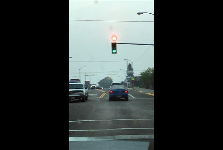 Taken at the stoplight at U.S. Hwy. 93 and First Street East in Polson, smoke makes the sun look like a red light.