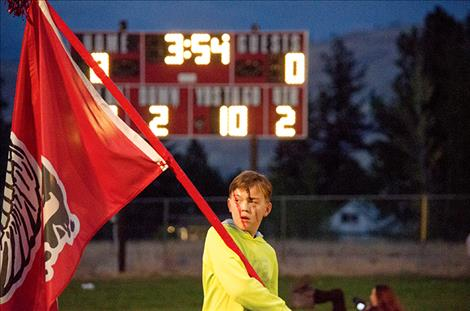 Edwin Koetter, 11, carries the Arlee flag during the football game.
