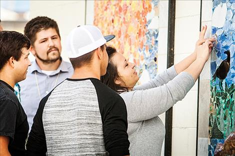 Terri Cleveland, along with her sons David and Nick, place a replica of her husband's police badge in the mosiac mural  at Riverside Park.