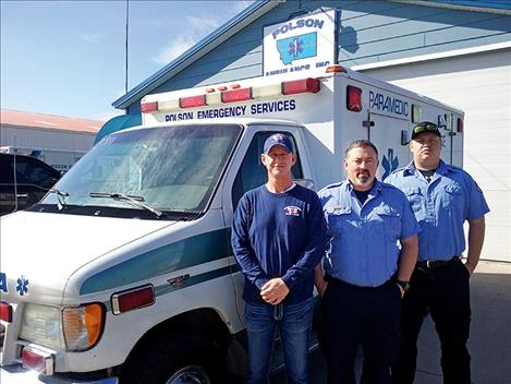 Tim Brester, Mike Cullen and Justin Brester stand next to an ambulance at the Polson station.