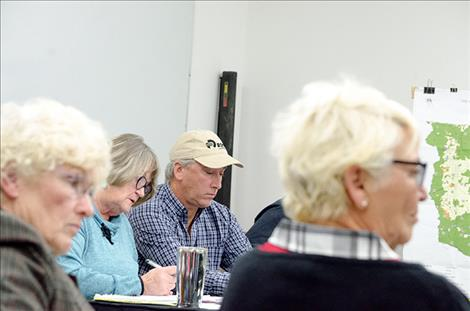 Flathead Joint Board of Control members look at agenda minutes during the regular meeting on Tuesday.