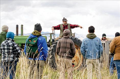 Dave Sturman talks to veterans, current military members, and their families about hooking a pigpen to a tractor and moving it to different locations on his farm.