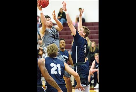 Zachary Mills shoots above defenders.