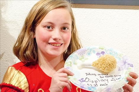 Elina Moore, 13, displays a rice cereal and marshmallow treat in the shape of a turkey drumstick. She is taking orders for her specialty holiday treats.