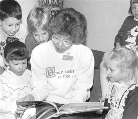 Marilyn Trosper reads to children during a story time hour at the library in Polson in the early 1990s. From left to right (front) are: Emily Fors, Marilyn Trosper and Andrea Mazurek. Behind them from left are: Ian Freemole, Kevin Owen and Jessica Bowers.