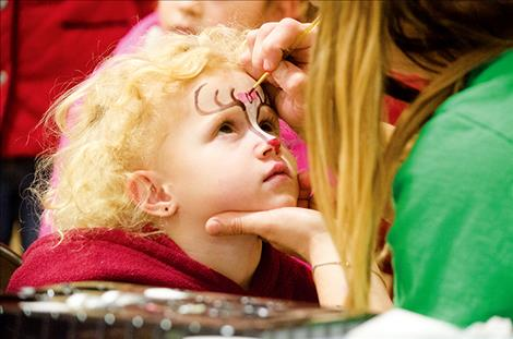 Alyeah Burckhard, 3, gets a reindeer painted on her face during the annual  St. Ignatius Chamber of Commerce holiday  carnival.