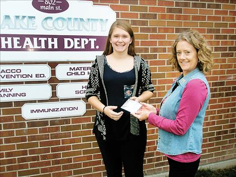 Alexis Terry, left, is given a $50 gift card by registered nurse Leigh Estvold.
