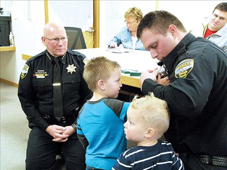 Far left, Jonathan Gilliland is sworn in as a Ronan Police reserve officer last week by Police Chief Ken Weaver.
