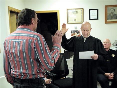 Outgoing Ronan Municipal Judge Justin L. Bartels swears in his replacement, Randy Melton, last week.