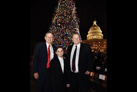 Senator Steve Daines, Bozeman sixth grader Ridley Brandmayr and Senator Jon Tester pose in front of the lit U.S. Capitol buliding's Christmas tree from Montana.