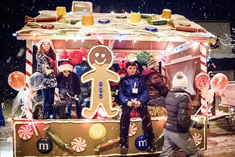 Children throw candy from a gingerbread house float.