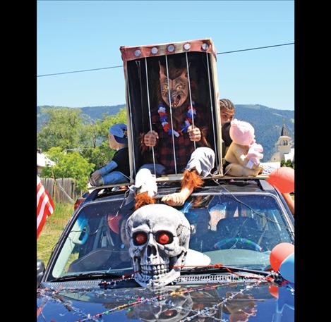 A caged creature howls and screams on top of a terrifying parade float.