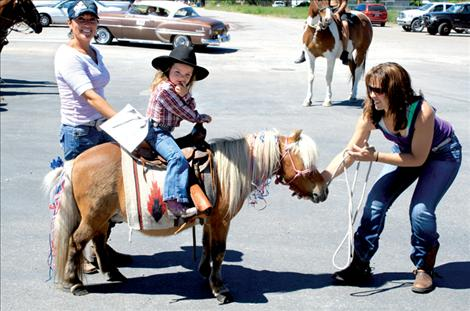 A miniature horse and cowgirl join the parade line at Arlee High School.