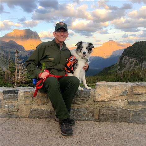 Park natural resources manager Mark Biel sits with border collie bark ranger, Gracie.
