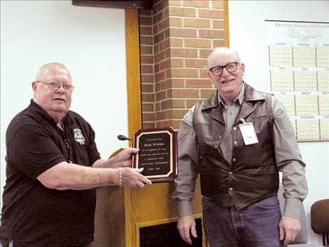 Rich Wiebke, left, receives a plaque from county commissioner Dave Stipe during a county employees' luncheon on Tuesday, Dec. 19.