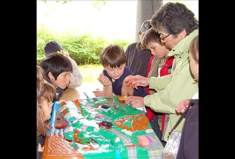 Flathead Lakers volunteer Libby Smith demonstrates and discusses nonpoint source pollution to students.The enviroscape model provided a powerful visual demonstration of how water and pollution flow through a watershed.