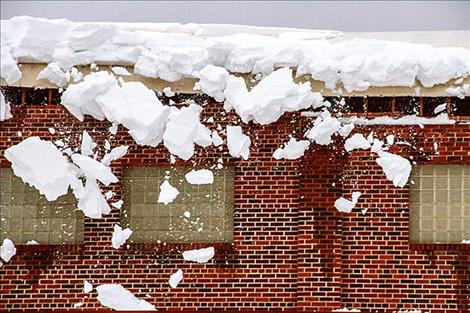 : Snow falls from the school's roof on Saturday afternoon.
