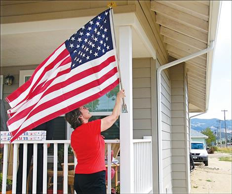 The owner of a newly-finished home in an affordable housing project in Boulder raises the flag on dedication day.