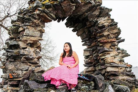 Carlee Rosbach sits on a stone arch between the Mission church and the Longhouse in St. Ignatius.