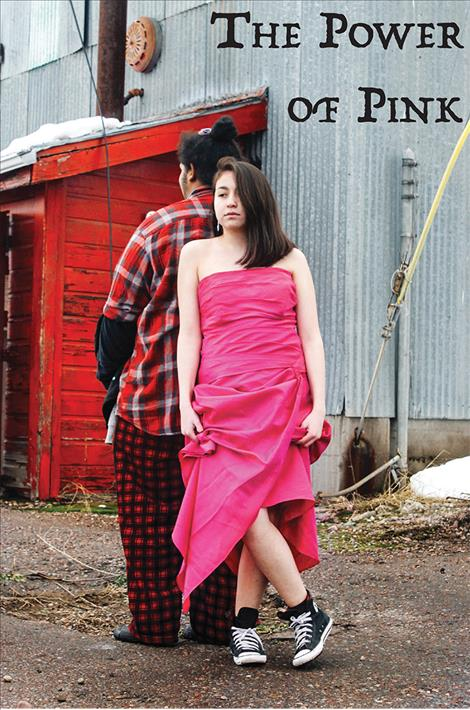 LeeAnn Yonkin wears a pink dress at the old lumber mill in Pablo while leaning on Zion Bolen.