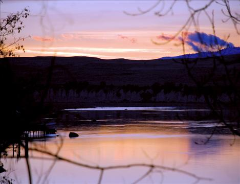 Sunset over the Flathead River paints the sky with streaks of pink and orange. The peaceful scene belies turmoil over a water rights compact making its way through the state legislature.