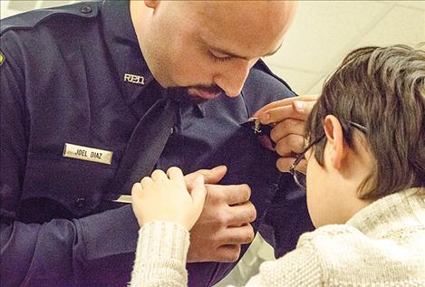 Ronan Officer Joel Diaz gets his badge pinned on by his son.