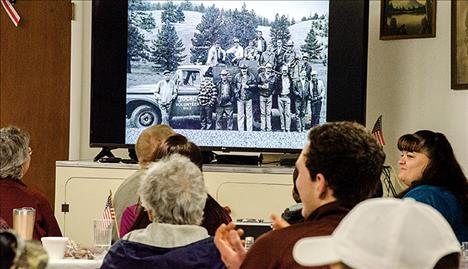 Volunteers and family members watch a slide show with a photo from around 1978 when Drew Hendrickson first joined the department. He is in the top row, far right.