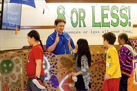 From a large decorated box, Principal Tyler Arlint high-fives students for reading thousands of books in February.