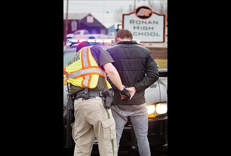 A highway patrol officer handcuffs a mock suspected drunk driver during a Ghost Out event.