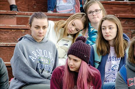 Somber faced students from St. Ignatius High School sit in the schools football bleachers after walking out of school to show respect for the students lost in the Florida school shooting