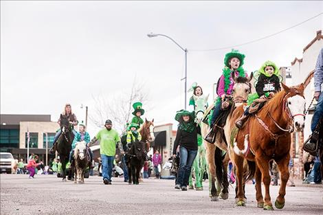 Horses and ponies, including a few green equines, join parade  participants.