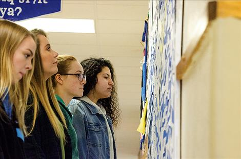 Sophia Tolbert, Leila Marsh, Brooklinn Hunt, and Addison Arlint read comments on a bulletin board where students anonymously posted comments about their experiences with suicide and suicide prevention.