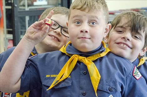 Nate Alder, 8, holds up an example of a uniform belt buckle the scouts will earn for holding the food drive.