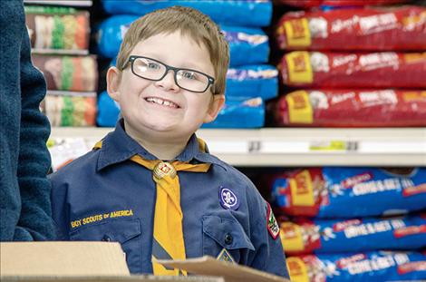With a smile, Cub Scout Elijah Bell, 8, asks people to donate.