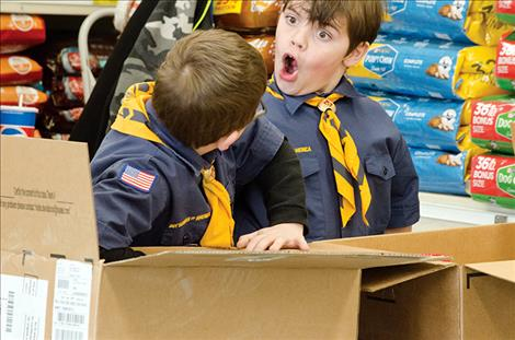 Cub Scout Tyler Miller, 8, is impressed with the amount of items people donated to the troop's food drive on Saturday.