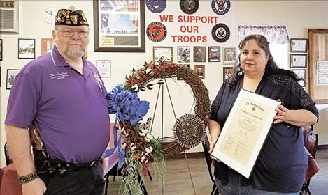 "District Commander Glen Sharbono, the wreath, and Rocky Davis holding her certificate, which reads: This certificate of appreciation is gratefully presented to Raquel Davis in recognition and sincere appreciation of outstanding service and assistance, which contributed to the advancement of The American Legion  programs and activities dedicated to God and Country. For the heartfelt wreath she made at the request of the District No. 4 Commander to be presented at the ""Healing Wall."" Presented by District No. 4,  Department of Montana, ""Thank you Rocky."""