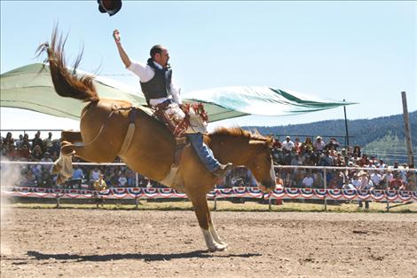A bareback rider loses his hat just before being bucked off.