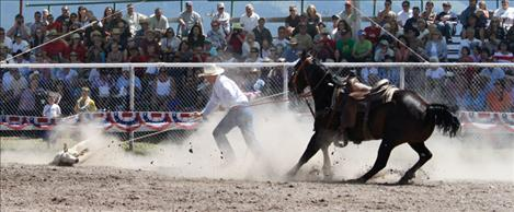 A calf gets taken down in front of a cheering crowd during the calf roping competition.