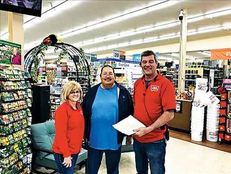 Beverley and Richard Osterwyk of True Value receive a rebate from Mission Valley Power for putting in new lights in their store.
