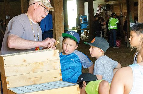 Chuck Lewis shows kids how a wooden bee hive is put together.