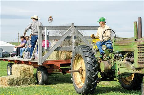 Curt Rosman drives a tractor while Sigurd Jensen talks to the kids about local weeds.