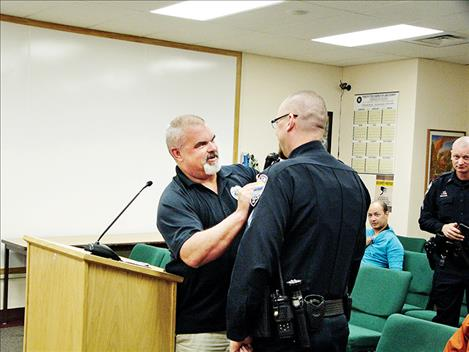 Polson Police Chief Wade Nash pins the corporal badge onto Corporal Mathieu Gfroerer during last week's Polson City Commission meeting.